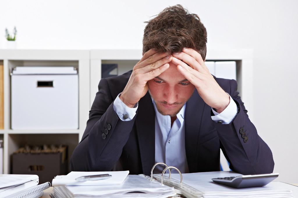 Schreibtisch voller akten  Mann mit Burnout über Akten gebeugt am Schreibtisch im Büro